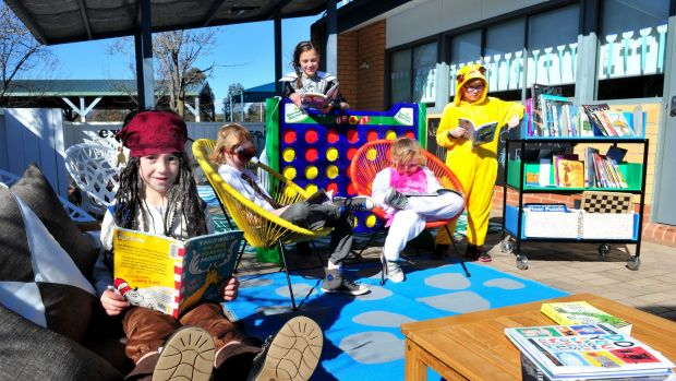 Reading in the new outdoor learning space at Bonython Primary school are, from left, Nek Stergiou,5 of Bonython, ...