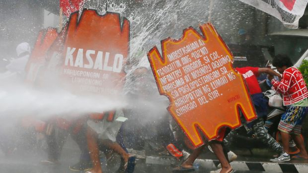 A fireman trains his hose on protesters as they force their way towards the US embassy in Manila on Wednesday.