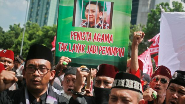 "Muslim protesters shout slogans as they hold up a placard with a picture depicting Jakarta Governor Basuki ""Ahok"" ..."