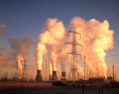 A petrochemical plant spews flue gas and steam at dawn. Such greenhouse gases are contributing to changes in climate.