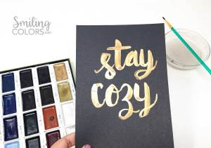 brush lettering on black paper with gold watercolors