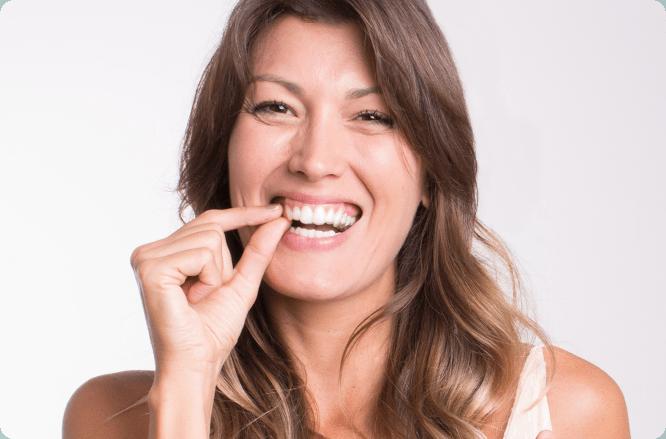 dentes alinhados em até 12 meses. Mulher colocando o aparelho invisível
