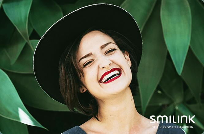 Mulher sorrindo com batom vermelho. maquiagem para realçar o sorriso