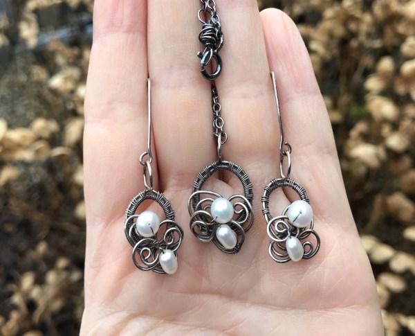 Håndflettet smykkesæt i sølv med hvide perler