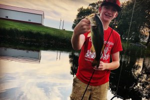 Boy in red shirt smiling and holding fish he caught