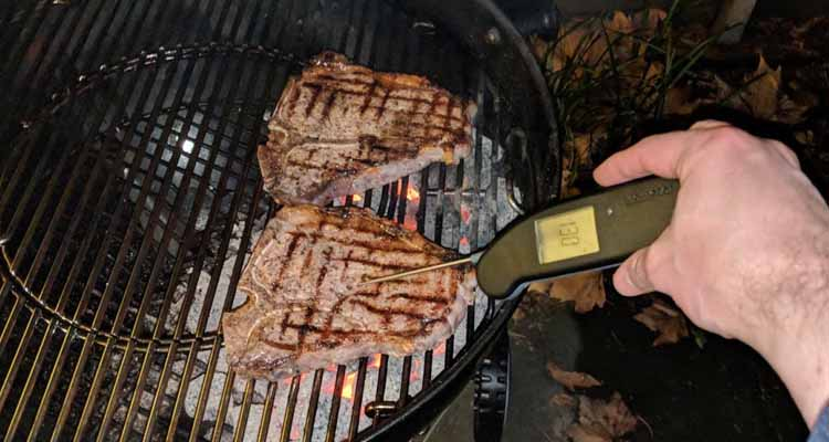 Checking steak with thermometer