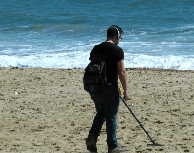 Man on the beach holding a metal detector
