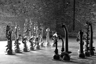 An oversized chess set built from found metal objects on a painted cement floor in an empty warehouse building at the American Visionary Arts Museum.