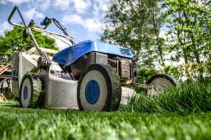 blue lawn mower on the green grass in the yard