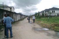 Building, Road, Town, Street, City, Footwear, Path, Vegetation, Plant, Shoe, Walking, Neighborhood, Pants, Rural, Countryside