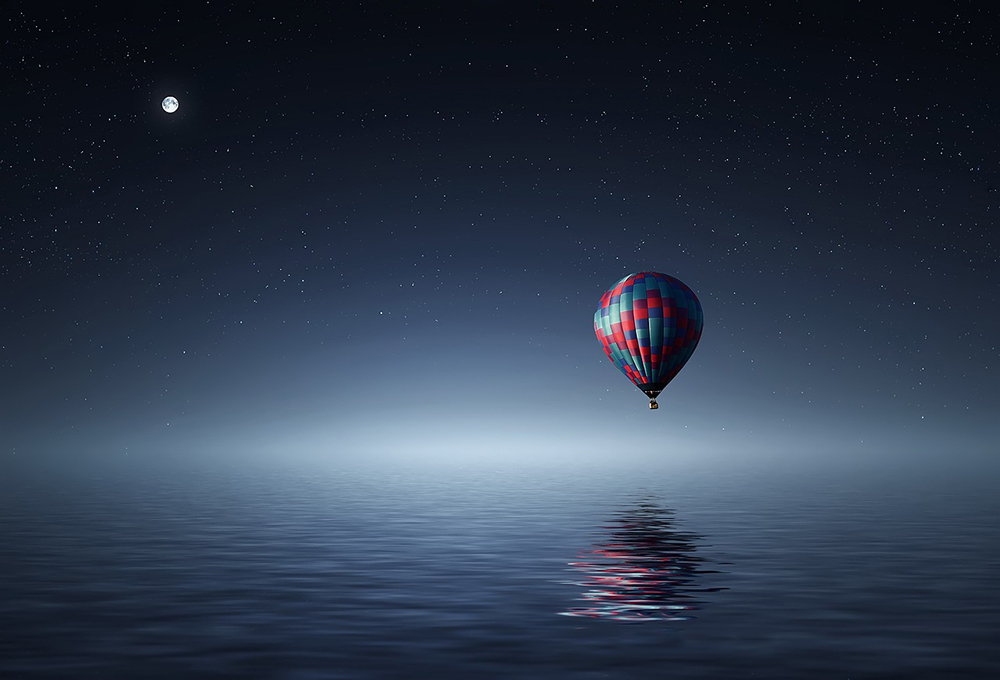 facing travel fears in a balloon above water night