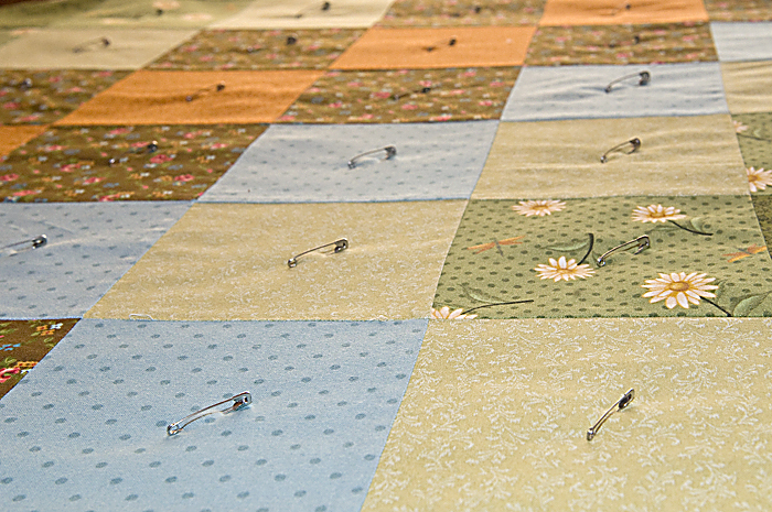 Sandwich quilt is pinned to secure the layers