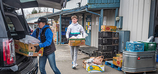 Volunteer delivery driver Joni Edelbrock and son Kodi load food boxes in their car