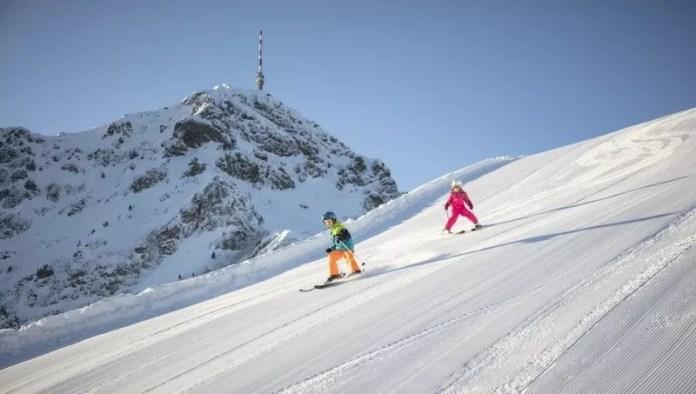 Kinderen scheuren de pistes af met de Kitzbüheler Horn op de achtergrond© Mirja Geh