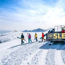 Jump on the Cirque Sled snowcat for easier access to the powder.