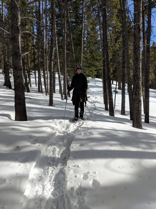 woman snowshoeing in a group of trees