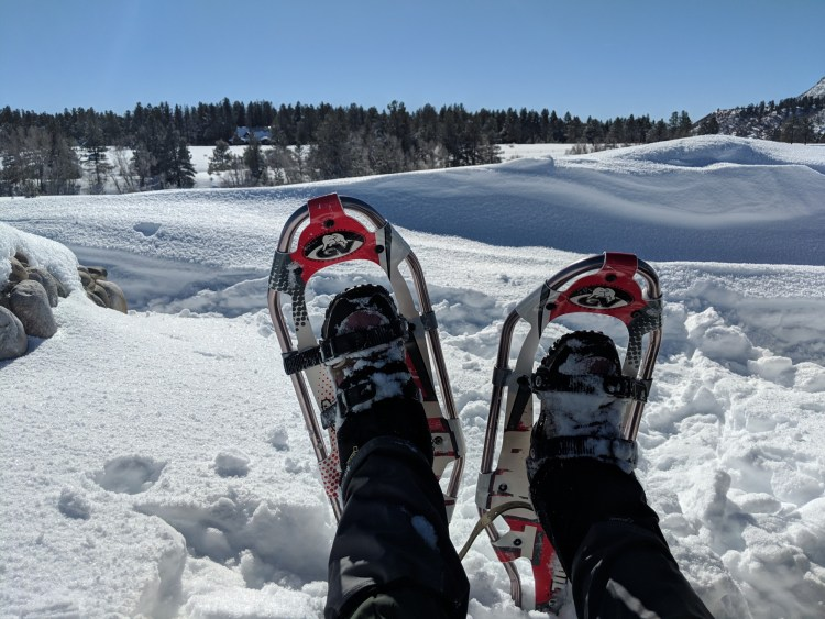 snowshoes while relaxing after snowshoe hike in Chama, NM