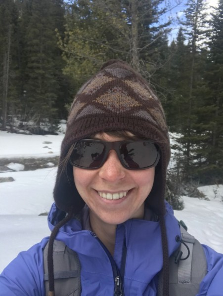woman smiling while wearing hat and sunglasses in winter