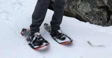 man in snowshoes pointing down towards snow