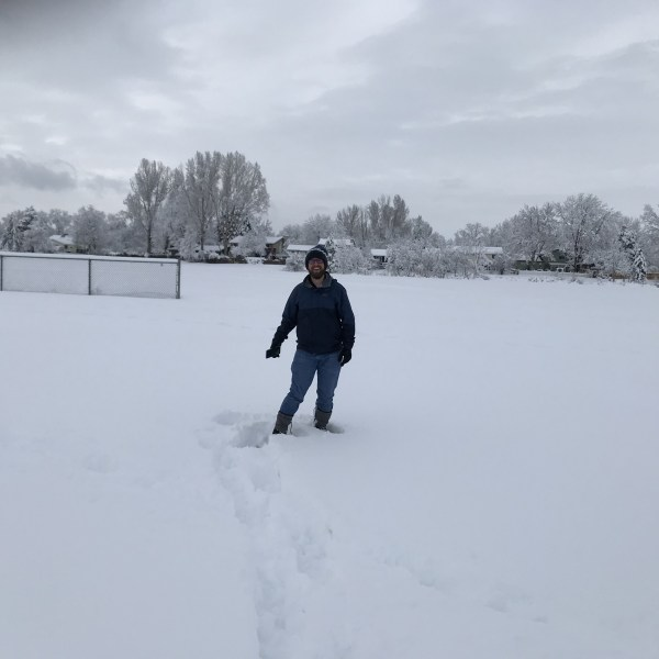 man snowshoeing in park, sinking to mid calf in foot of fresh snow