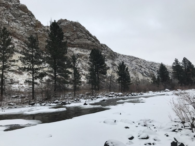 snow, river, and hill in background
