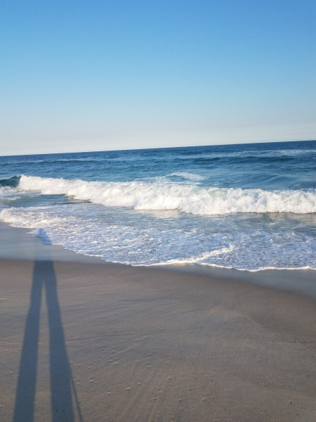 shadow on the beach with waves in background