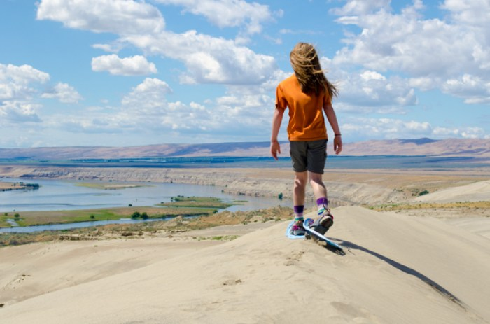 snowshoeing in summer: girl using snowshoes on top of a sand dune