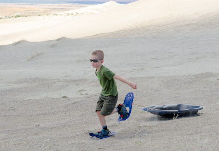 boy sandshoeing and pulling a sled