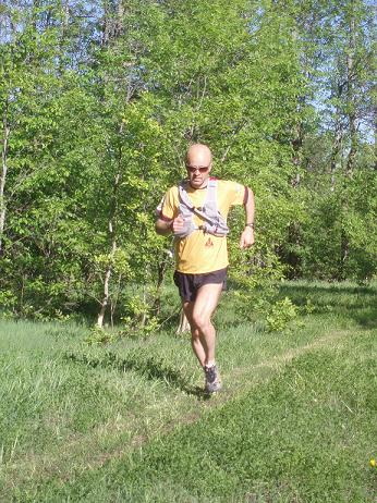 Derrick Spafford trail running with hydration pack during the summer