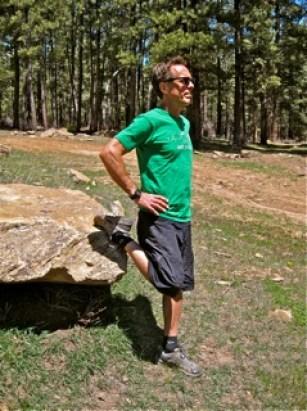 man stretching his leg using a rock