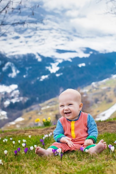baby smiling and sitting in flowered meadow with snowy mountains in background
