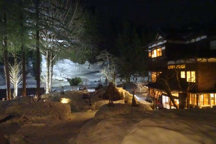 Japanese Inn with candles in snow lighting the walkways