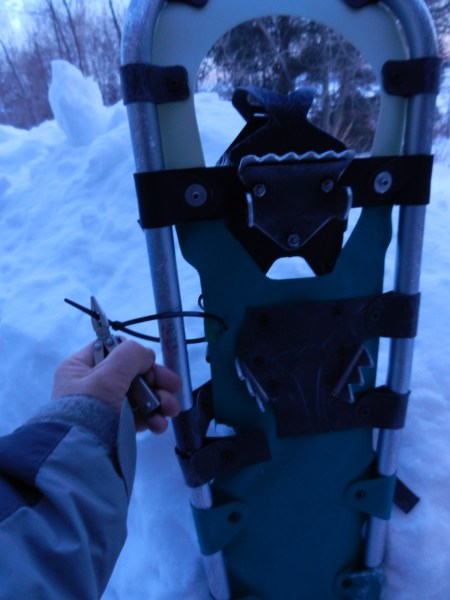 snowshoe repair kit: close up of person use a plastic tie to attach the decking to the snowshoe frame