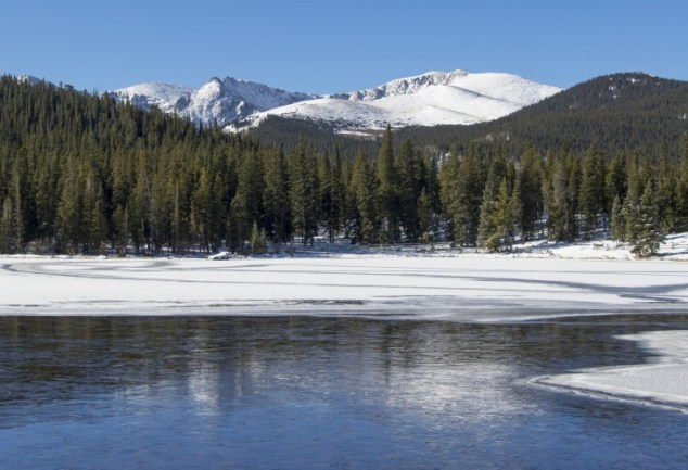 lake with ice and mountains in trees in background
