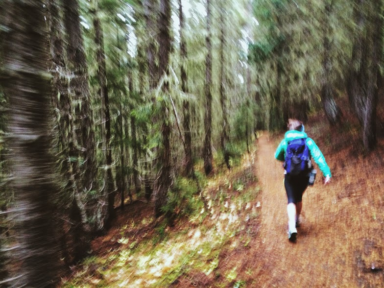 woman running on a trail in a forest