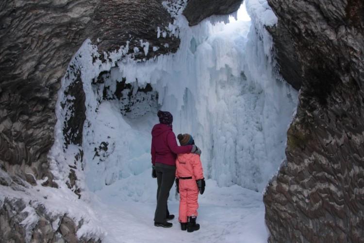 woman and child standing underneath natural bridge at Emerald Lake BC