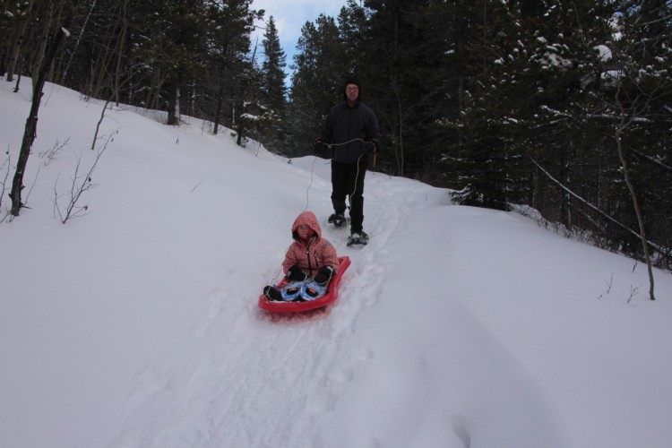 man guiding a sled with child in it down a snowy hill