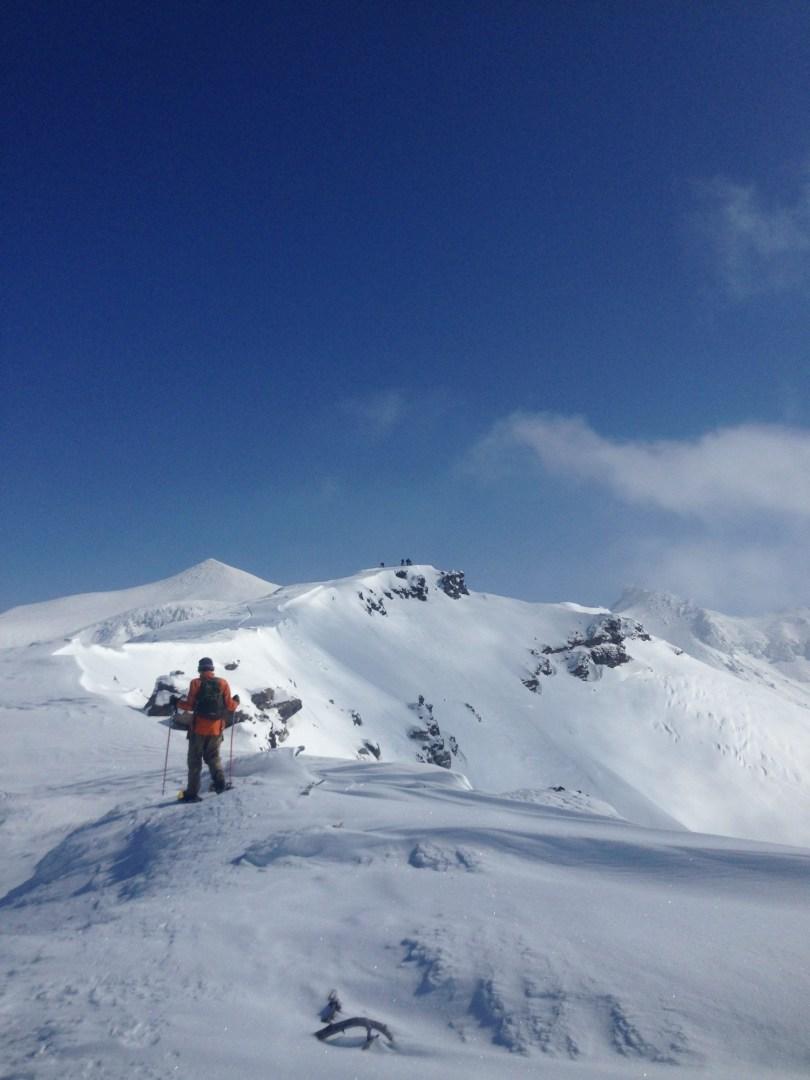 man walking on mountain peak with blue skies- Goodmacher