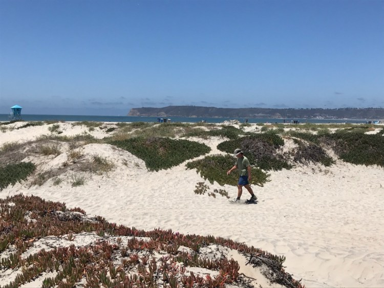 man in background using snowshoes on sand with ocean view in distance and dunes all around