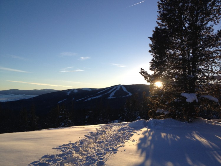 trail with Maverick Mountain and sun between trees on snowy trail