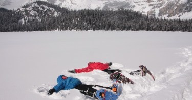 adult and child laying in the snow on snowshoes