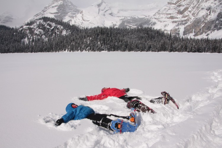 snowshoeing is not boring: adult and child laying in the snow on snowshoes