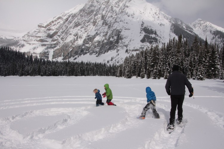 kids and adult running after each other on snowshoes in games of pie tag