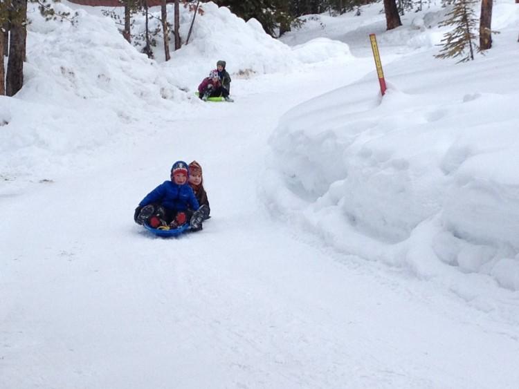 kids sledding down snowy road