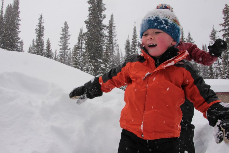 snowshoeing is not boring: child having fun on snow while father is chasing him