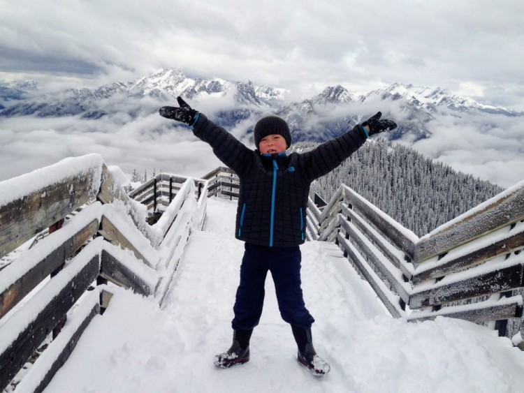 child with arms up after riding Banff Gondola