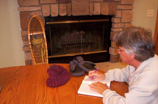 man writes in journal at table with snowshoes in background