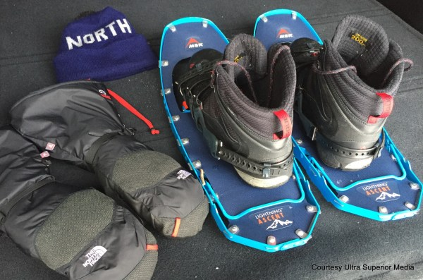 flat lay of snowshoes, boots, gloves, hat