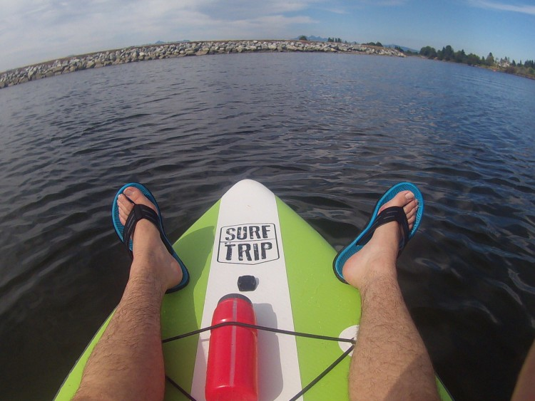 legs resting on paddleboard with water and rocks in background