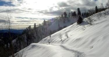 man snowshoeing on trail in Uinta Mountains Utah